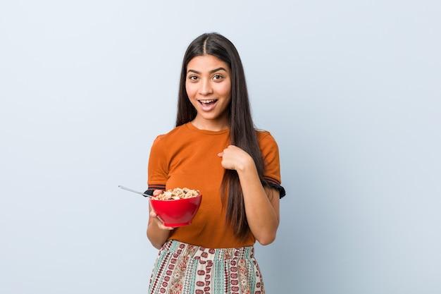 Jonge arabische vrouw die een graangewassenkom houdt verrast richtend op zich, breed glimlachend.