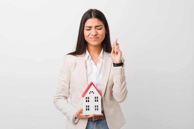 Jonge arabische vrouw die een huispictogram houdt dat vingers kruist voor het hebben van geluk