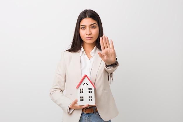Jonge arabische vrouw die een huispictogram houdt dat zich met uitgestrekte hand bevindt die eindeteken toont, dat u verhindert.