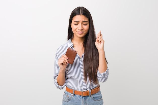 Jonge arabische vrouw die een portefeuille houdt die vingers kruist om geluk te hebben