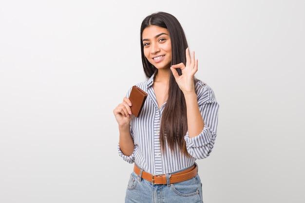 Jonge arabische vrouw die een portefeuille vrolijk en zeker houdt die ok gebaar toont.