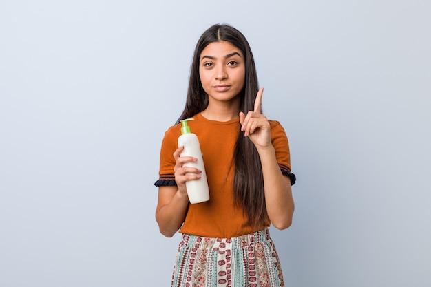 Jonge arabische vrouw die een roomfles houdt die nummer één met vinger toont.