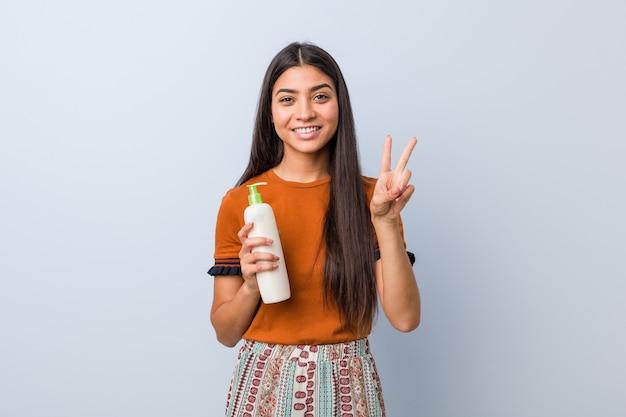 Jonge arabische vrouw die een roomfles houdt die nummer twee met vingers toont.