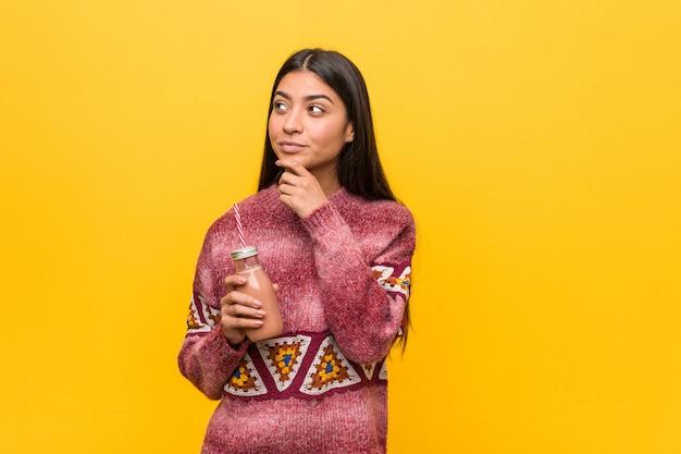 Jonge arabische vrouw die een smoothie houdt die zijdelings met twijfelachtige en sceptische uitdrukking kijkt.