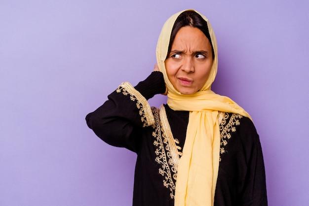 Jonge arabische vrouw die een typisch arabisch kostuum draagt dat op purpere achtergrond wordt geïsoleerd die achterkant van het hoofd aanraakt, nadenkt en een keuze maakt.