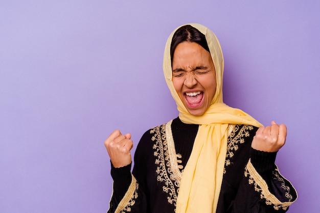 Jonge arabische vrouw die een typisch arabisch kostuum draagt dat op purpere achtergrond wordt geïsoleerd die vuist opheft na een overwinning, winnaarconcept.