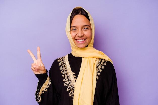 Jonge arabische vrouw die een typisch arabisch kostuum draagt dat op purpere achtergrond wordt geïsoleerd, vreugdevol en zorgeloos toont een vredessymbool met vingers.