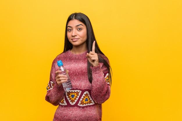 Jonge arabische vrouw die een waterfles houdt die nummer één met vinger toont.