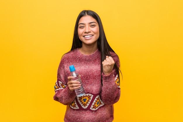 Jonge arabische vrouw die een waterfles onbezorgd en opgewekt toejuichen houdt. overwinning concept.