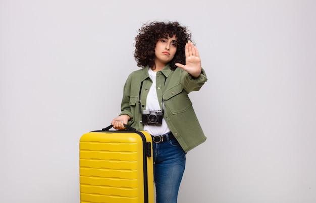 Jonge arabische vrouw die ernstig, streng, ontevreden en boos kijkt die open palm toont die het reisconcept van het stopgebaar maakt
