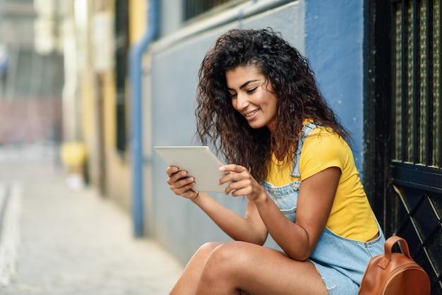 Jonge arabische vrouw die haar digitale tablet in openlucht bekijkt.