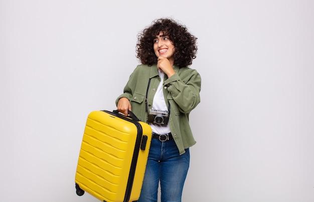 Jonge arabische vrouw die met een gelukkige, zelfverzekerde uitdrukking glimlacht met hand op kin, zich afvraagt en naar het zijreisconcept kijkt