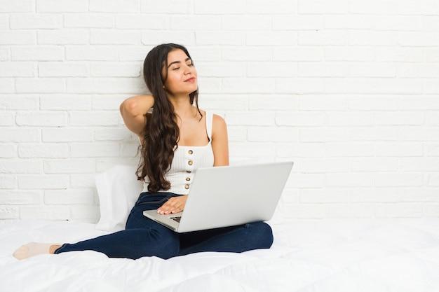 Jonge arabische vrouw die met haar laptop aan het bed werkt dat aan nekpijn lijdt vanwege sedentaire levensstijl.