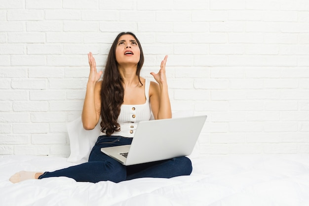 Jonge arabische vrouw die met haar laptop bed gillende hemel werkt, die gefrustreerd omhoog kijkt.