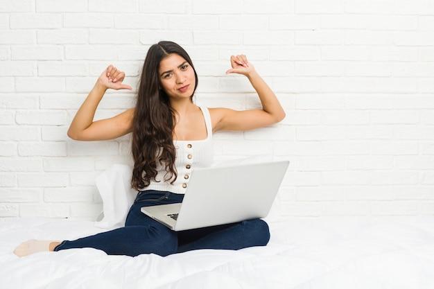Jonge arabische vrouw die met haar laptop op het bed werkt, voelt zich trots en zelfverzekerd, bijvoorbeeld om te volgen.