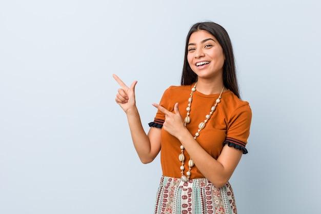 Jonge arabische vrouw die met wijsvingers aan een exemplaarruimte richt, opwinding en wens uitdrukt.