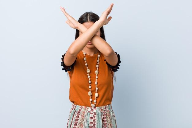 Jonge arabische vrouw die twee wapens gekruist houdt, ontkenning.