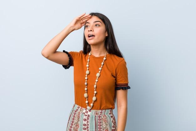 Jonge arabische vrouw die ver weg houdend hand op voorhoofd kijkt.