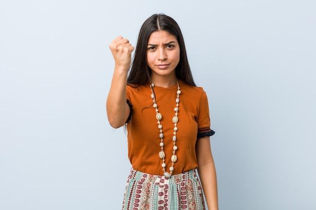 Jonge arabische vrouw die vuist toont aan camera, agressieve gelaatsuitdrukking.