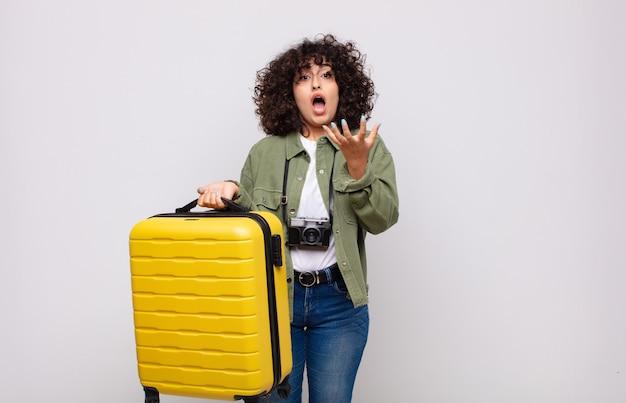 Jonge arabische vrouw die wanhopig en gefrustreerd, gestrest, ongelukkig en geïrriteerd kijkt, schreeuwend en schreeuwend reisconcept