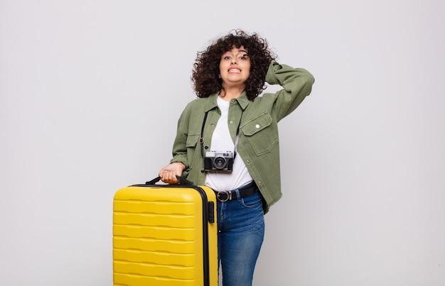 Jonge arabische vrouw die zich gestrest, bezorgd, angstig of bang voelt, met de handen op het hoofd, in paniek raakt bij het reisconcept van de fout