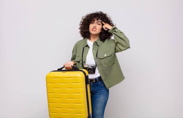 Jonge arabische vrouw die zich verward en verbaasd voelt en laat zien dat je gek, gek of gek bent op reisconcept