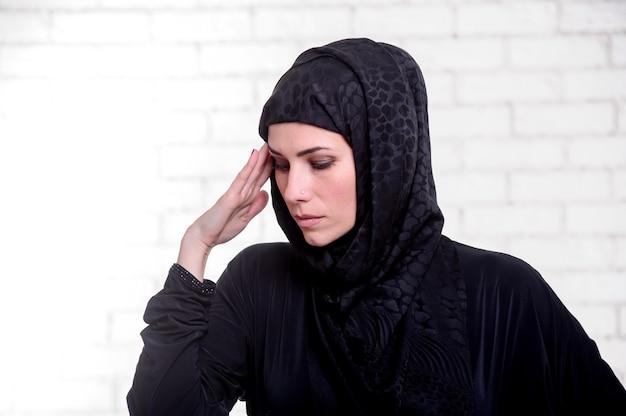 Jonge arabische vrouw gekleed in traditionele arabische kleding poses binnen.