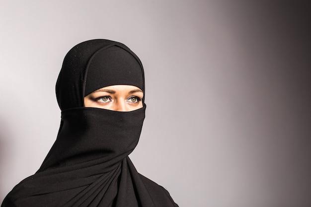 Jonge arabische vrouw in hijab of niqab.