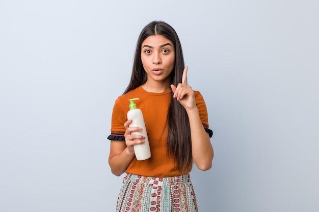 Jonge arabische vrouw met een crème fles met een geweldig idee, concept van creativiteit.