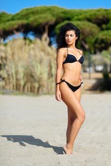 Jonge arabische vrouw met mooi lichaam in badkleding op een tropisch strand.