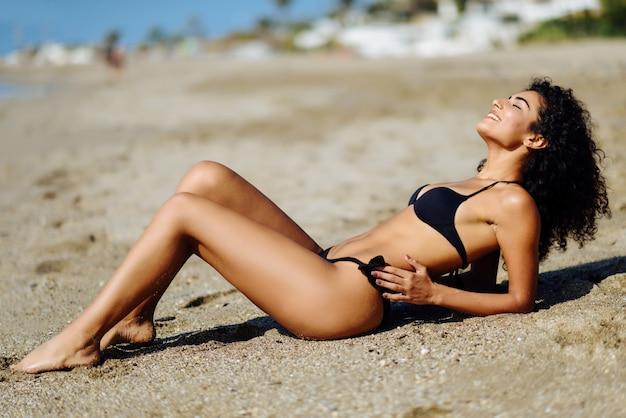 Jonge arabische vrouw met mooi lichaam in swimwear liggend op het strandzand