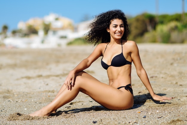 Jonge arabische vrouw met mooi lichaam in swimwear zitting op het strandzand.