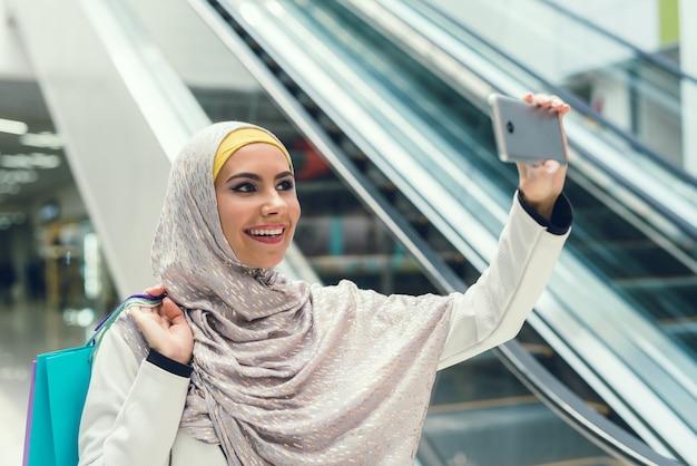 Jonge arabische vrouw nemen selfie in moderne winkelcentrum.
