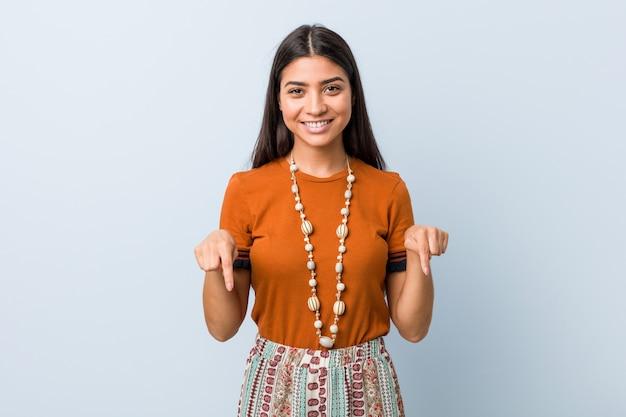 Jonge arabische vrouw wijst naar beneden met vingers, positief gevoel.
