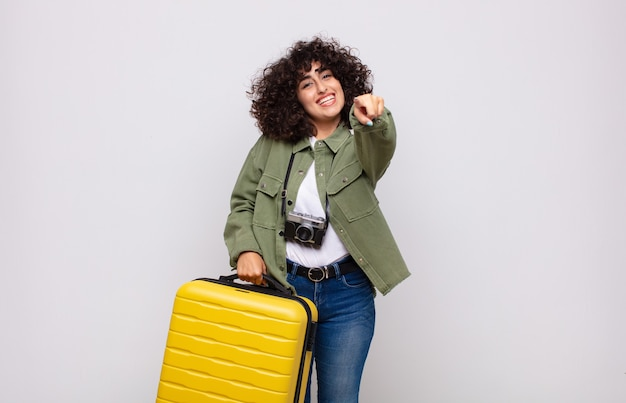 Jonge arabische vrouw wijzend op camera met een tevreden, zelfverzekerde, vriendelijke glimlach, die je reisconcept kiest