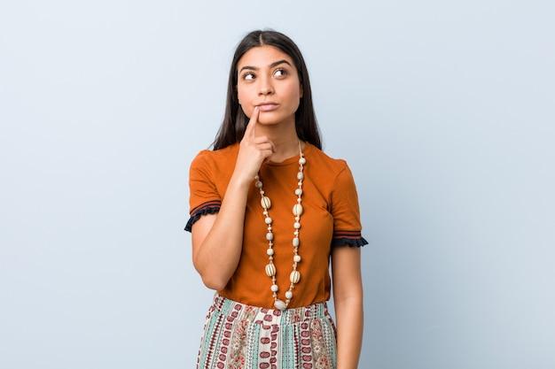 Jonge arabische vrouw zijwaarts op zoek met twijfelachtige en sceptische uitdrukking.
