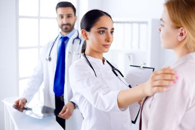 Jonge arabische vrouwelijke arts legt de diagnose uit aan een patiënt in een ziekenhuis