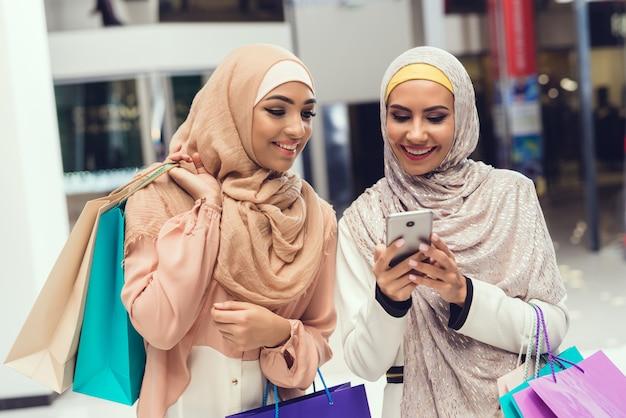 Jonge arabische vrouwen met behulp van smartphone met vriend