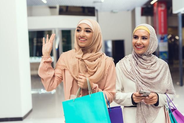 Jonge arabische vrouwen met pakketten permanent in winkelcentrum.