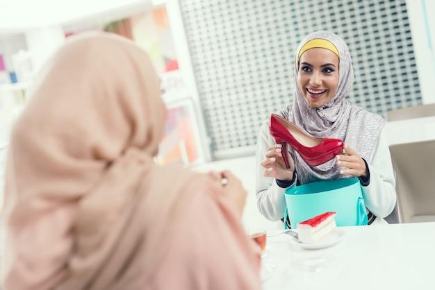 Jonge arabische vrouwen zitten in cafe in moderne mall.