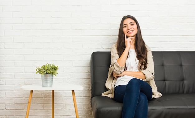 Jonge arabische vrouwenzitting op bank het glimlachen gelukkig en zeker, wat betreft kin met hand.