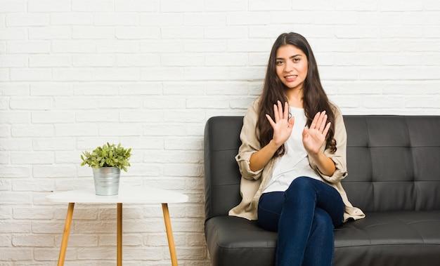 Jonge arabische vrouwenzitting op de bank die iemand verwerpen die een gebaar van afschuw tonen.
