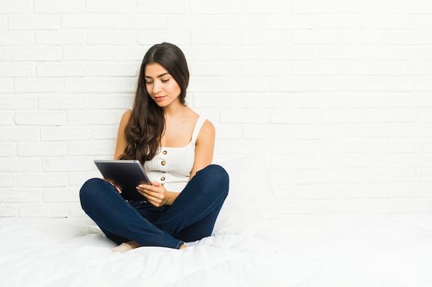 Jonge arabische vrouwenzitting op het bed die een tablet gebruiken