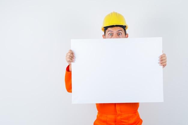Jonge arbeider die leeg canvas in uniform, helm houdt en verbaasd kijkt.
