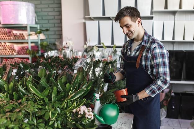 Jonge arbeider in blauwe schort bij bloemenwinkel