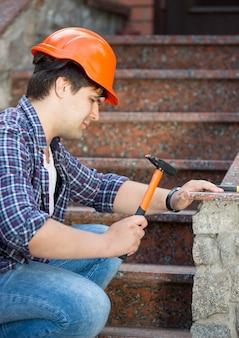 Jonge arbeider in rode helm die oude steentrap herstelt