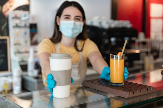 Jonge arbeidersvrouw die afhaalbestelling levert aan klant in coffeeshop tijdens uitbraak van coronavirus