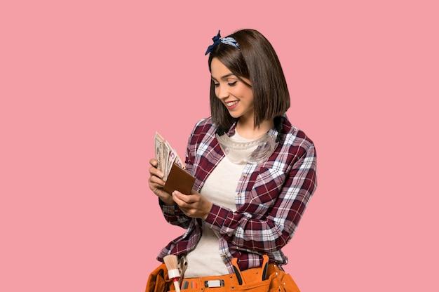 Jonge arbeidersvrouw die een portefeuille op geïsoleerde roze muur houdt
