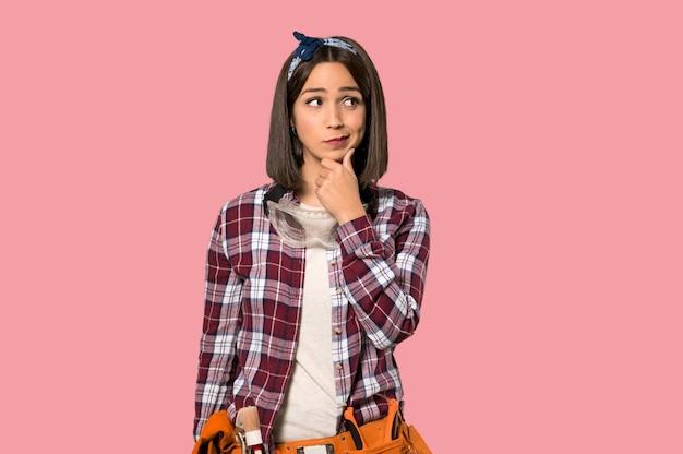 Jonge arbeidersvrouw die op geïsoleerde roze muur denkt