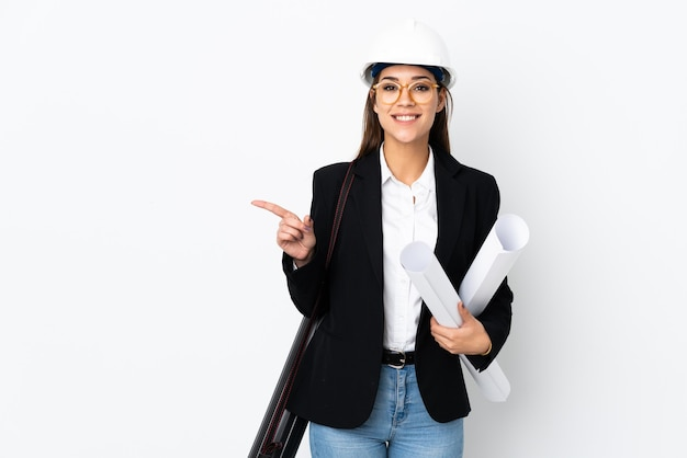 Jonge architect blanke vrouw met helm en blauwdrukken e